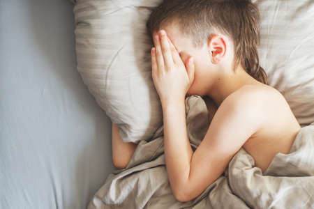boy sleep in the bed. the child lies on a pillow and covers his face with his hands 写真素材