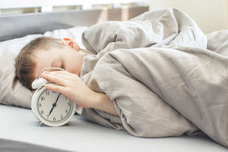 boy lying on the bed and stopping alarm clock in the morning. childs hand reaching for the alarm clock to turn it off.