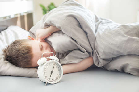 the boy lies on the bed in the morning and covers his ears so as not to hear the alarm clock. child does not want to wake up