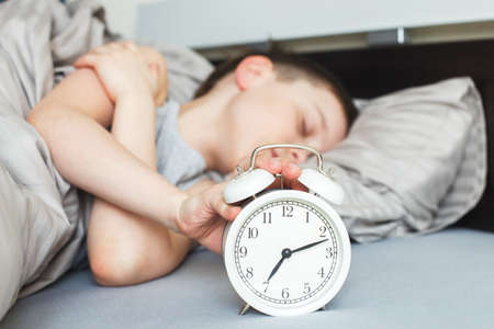 boy lying on the bed and stopping alarm clock in the morning. childs hand reaching for the alarm clock to turn it off. 写真素材