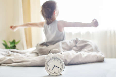 little boy sitting and stretching in the bed at home in the morning on a window background with alarm clock
