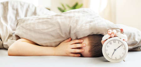 boy lying on the bed under a blanket and stopping alarm clock in the morning. childs hand reaching for the alarm clock to turn it off. banner