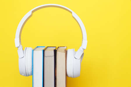 Audio book concept with modern white headphones and hardcover book on a yellow background. Listening to a book. E-learning. Copyspace.