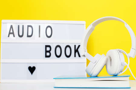 Audio book concept with modern white headphones and hardcover book on a yellow background. Listening to a book. E-learning. Copyspace. inscription on a lightbox 写真素材