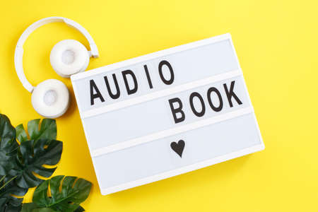 the inscription audiobook on a light box with modern white headphones on a yellow background. Listening to a book. E-learning.