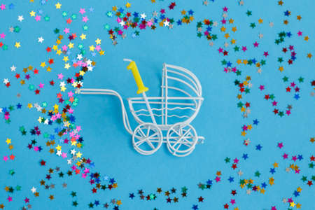 One year birthday party .baby stroller with a candle in the form of the number one on a blue background with stars confetti sequins 写真素材