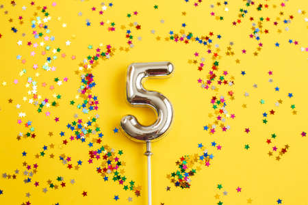 five years birthday party. number five with a multicolored confetti in the form of stars on a yellow background 写真素材