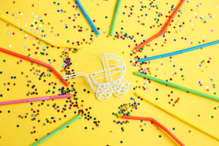 birthday party. baby stroller with a stars confetti sequins and multicolored drinking straws on yellow background