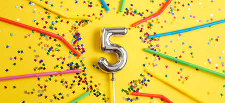 five years birthday party. number five with a multicolored confetti in the form of stars and drinking straws on a yellow background. banner