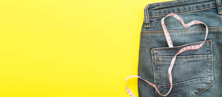 Close up of blue jeans with measure tape in the pocket in form of a heart. concept of a healthy lifestyle and diet with love to your body.banner