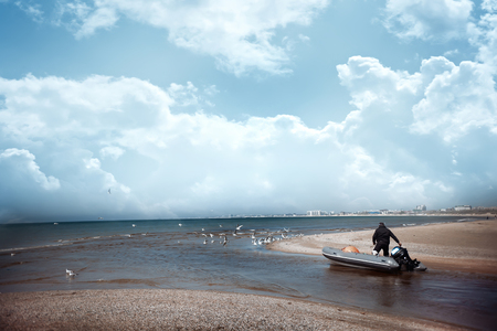 the man goes next to his motor boat and they go to the sea Stock Photo