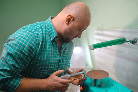 Master sharpens scissors on special equipment for sharpening tool