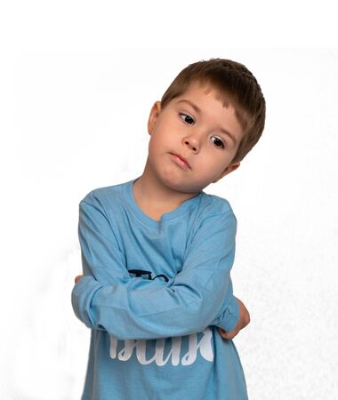 little boy pondered and crossed his arms on his stomach Фото со стока