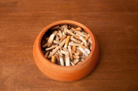 Cigarette in clay ashtray photo