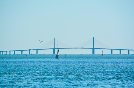 A sail boat on Tampa Bay sailing to the distant Sunshine Skyway Bridge and the Gulf of Mexico Imagens