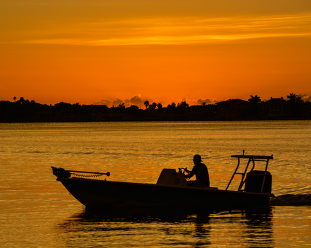 Sunset with the silhouette of a boat on the inter coastal in Belleair Bluffs, Florida Stock Photo