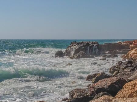 Waves splashing on the rocks of the Mediterranean coast in Caesarea National Park. Sharon, Israel