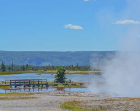 A walkway to view a hot springs with boiling water at the Lower Geyser Basin. With steam rising in Yellowstone National Park, Wyoming