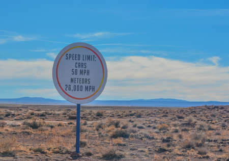 Car and Meteor speed limit sign. On the road to the Meteor Crater Natural Monument on the Arizona Rocky Plain
