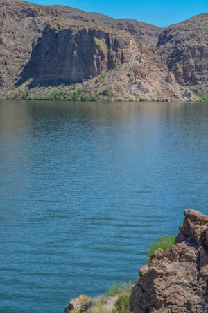 Beautiful desert rock formations line this secluded, Canyon Lake in Tortilla Flat, Tonto National Forest, Arizona 免版税图像