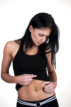 skinny woman: Skinny woman pinching her stomach