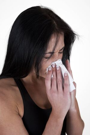 Woman sneezing into a tissue  photo