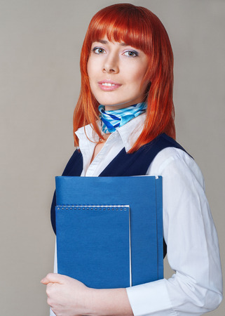 vernal: Young red-haired girl holding a folder and notebook in the form of