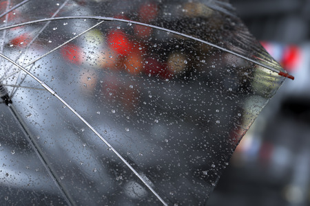 close: Transparent umbrella with rainy drops close up on street city lights background. 3D illustration