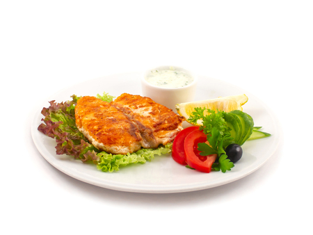 Fried sturgeon on lettuce leaves with fresh vegetables, parsley leaves, a slice of lemon and olive on a plate close up on a white background