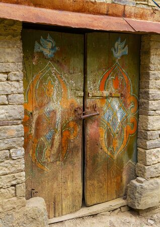 The door of the old house of the mountaineers in the Dagestan aul Harbuk. Vintage door of an old house in daylight. Handwork. Ethnic culture of the peoples of the Caucasus. Cracked paint