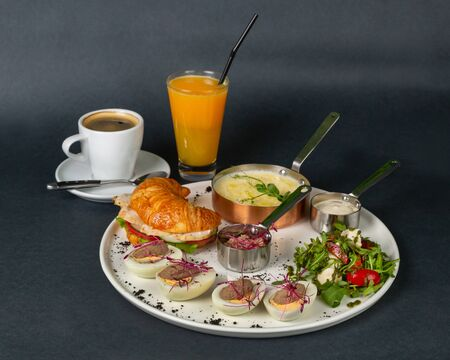 Rich breakfast - corn porridge, croissant with sliced chicken, rucola, tomato and cheese salad with pesto sauce, boiled chicken eggs with chicken pate. Everything is decorated with microgreens. Plate on a dark background. Left glass of orange juice with a straw and a cup of coffee Zdjęcie Seryjne
