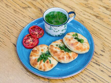 Breakfast in Tatar. Pies decorated with chopped herbs on a plate. Hot broth mug and slices of grilled tomato