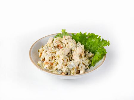 Salad with ham, bell pepper, mushrooms, pickles, white sauce, on a white plate. Decorated with lettuce, side view, selective focus