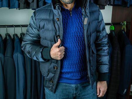 Un joven con un suéter azul y jeans demuestra una chaqueta de invierno. Sombras de azul. Ropa de abrigo en una boutique
