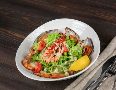Salad with mussels, king prawns, cherry tomatoes and lettuce. Sprinkled with grated Parmesan. On the surface of dark abandoned planks. Lemon slice. Close up, side view