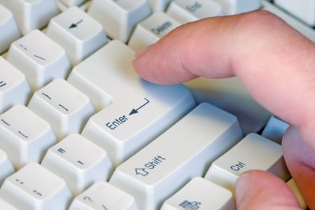 Male finger hitting the enter key on a keyboard.