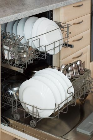 Open built-in dishwasher with set of clean dishes, plates, glasses and forks with spoons.