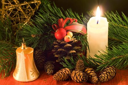 Christmas scene with golden bell, white candle and cones in low light.