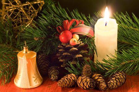 simbolos religiosos: Escena de Navidad con campana dorada, vela blanca y conos con poca luz.  Foto de archivo