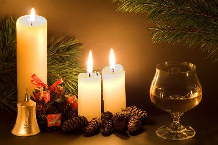 religious event: Christmas scene with white candles, cones, bell and glass of wine in low light. Stock Photo