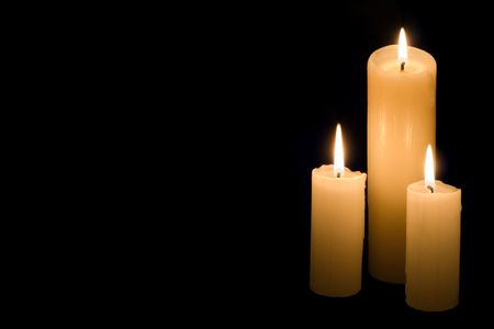 Three white candles on black background with large copy space.