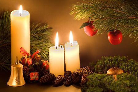 Christmas scene with white candles, cones, bell and a mushroom in green moss in low light. Stock Photo