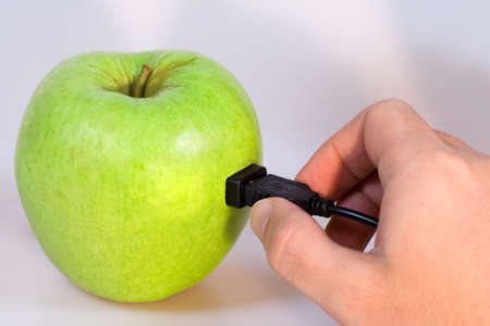 Green apple connected via usb cable with a hand holding the plug.