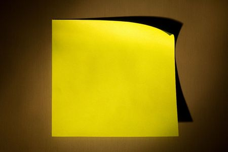 Blank yellow adhesive post-it note stuck on stainless steel surface of refrigerator in warm yellow illuminating cone. Stock Photo