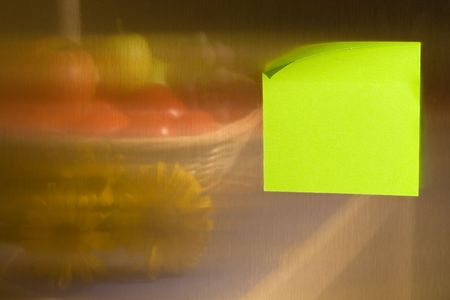 Blank green-yellow adhesive post-it note stuck on stainless steel surface of refrigerator mirroring fruit in a straw basket and some flowers. photo