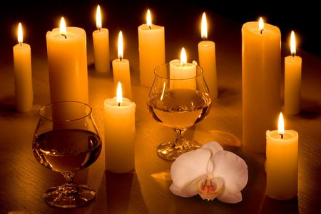 Romantic table with candles, two wine glasses and white orchid.