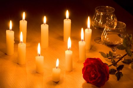 Romantic table with flaming heart of candles, two glasses of wine and red rose. Stock Photo