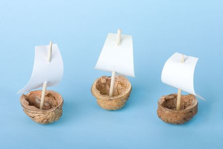 Three little boats made from walnut shell on blue background.