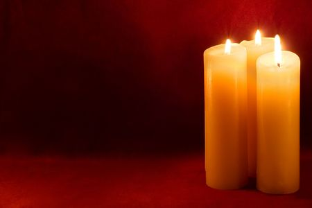 Three burning yellow-white candles on scarlet background