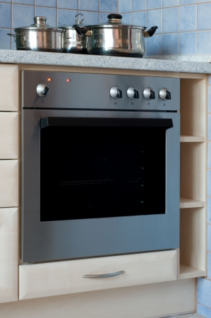 Built-in stainless steel electric oven with cooking pots on stove Stock Photo